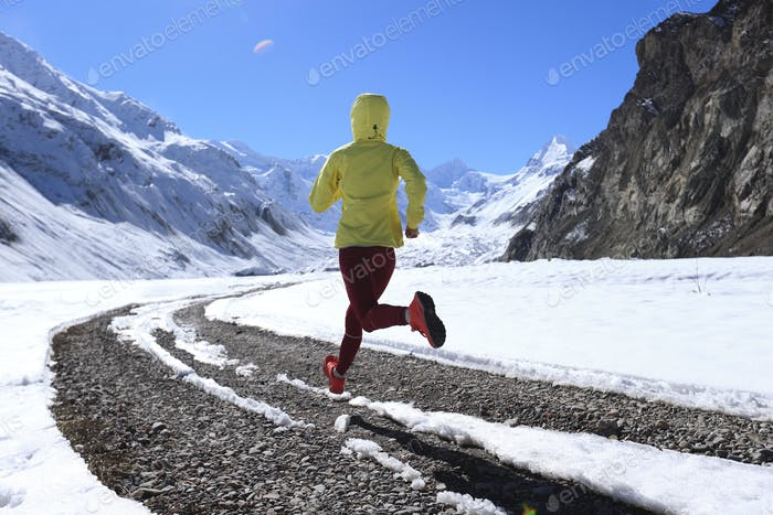 Woman trail runner cross country running  in winter mountains