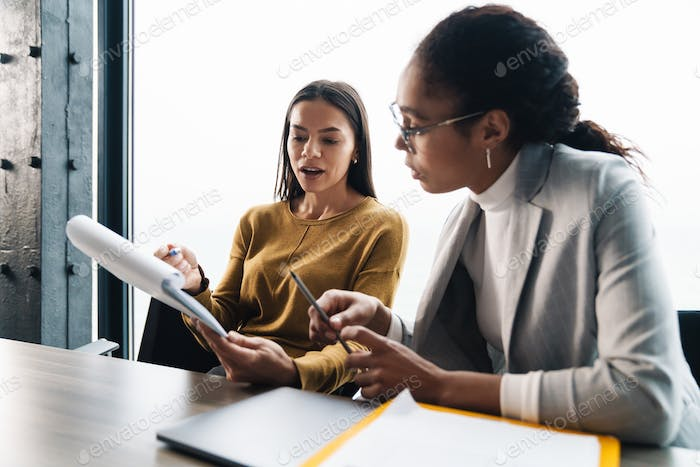 Portrait of businesswomen sitting by desk while working in office