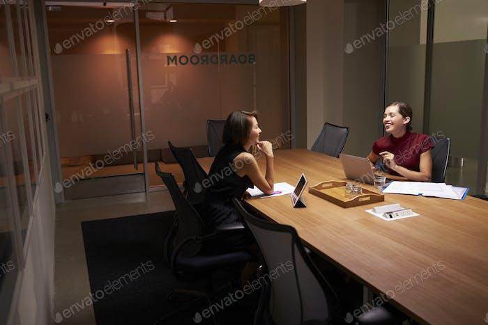 Two businesswomen working late in an office share a joke