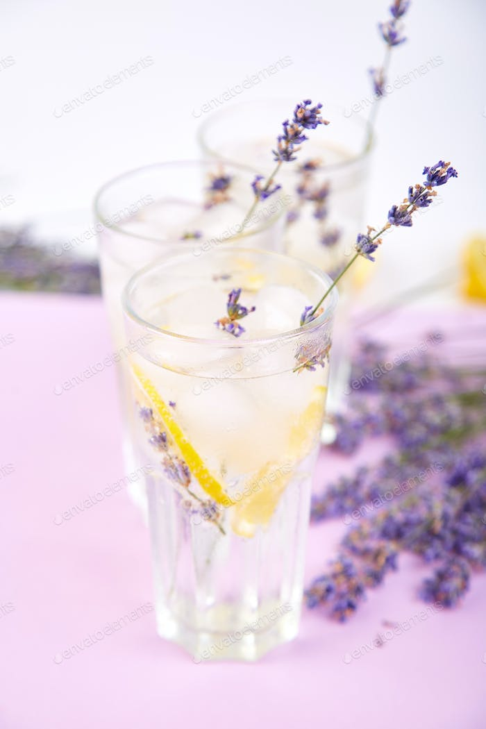 Lavender lemonade with lemon and ice on purple background