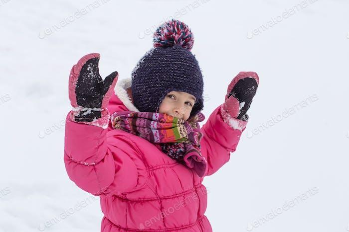 Chica cálidamente vestida se regocija en la nieve que cae de cerca.