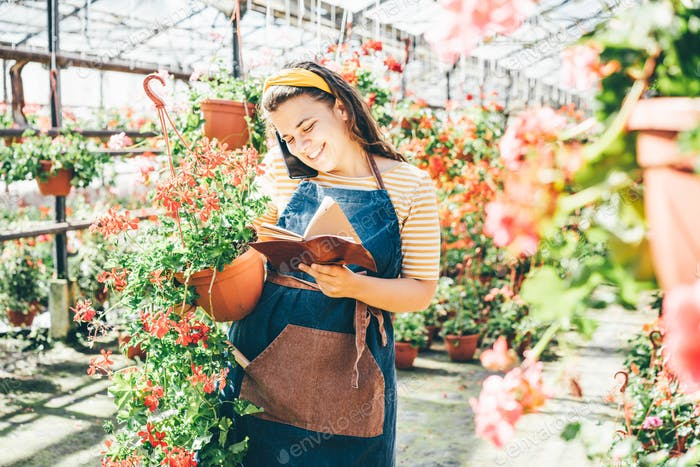 woman gardener in blue apron talks on smartphone writing in paper notebook