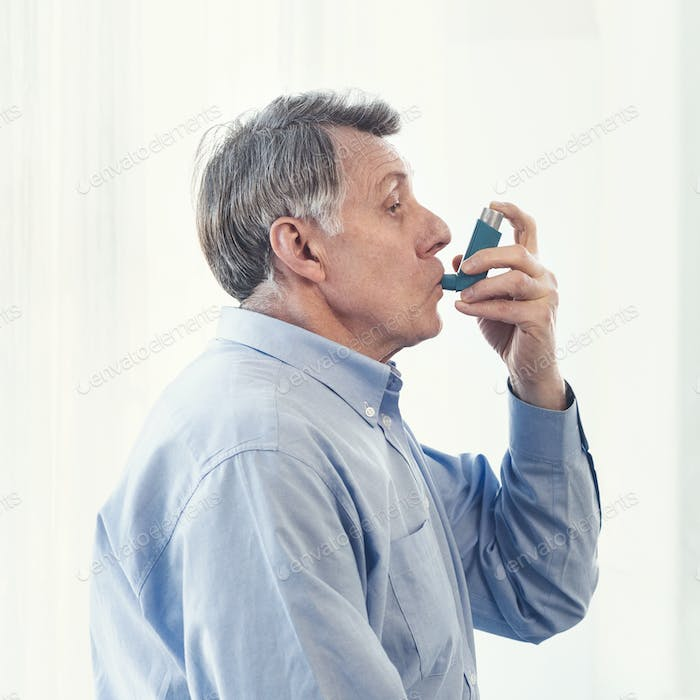 Elderly man using asthma inhaler for allergies