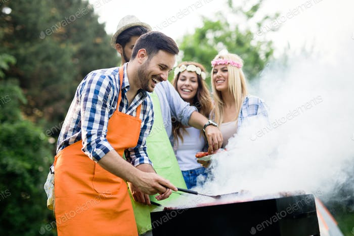 Group of happy friends having barbecue party in forest