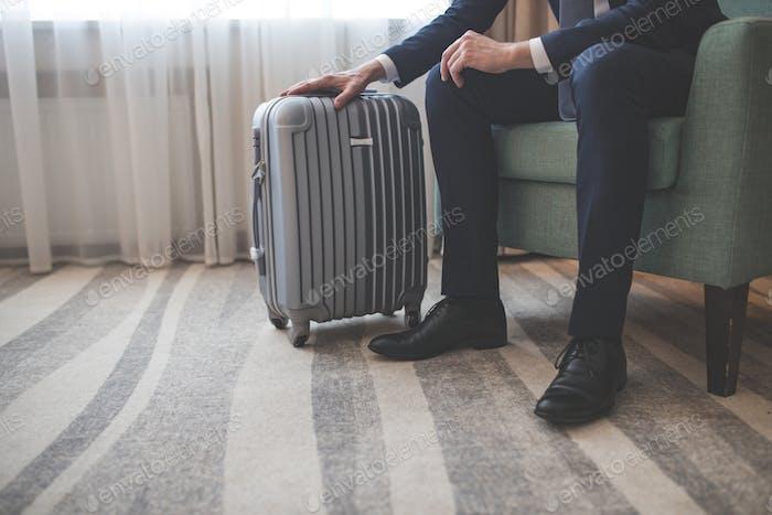 Junger Geschäftsmann mit einem Koffer drinnen