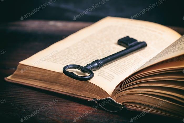 Schlüssel auf einem Vintage-Buch auf Holzhintergrund