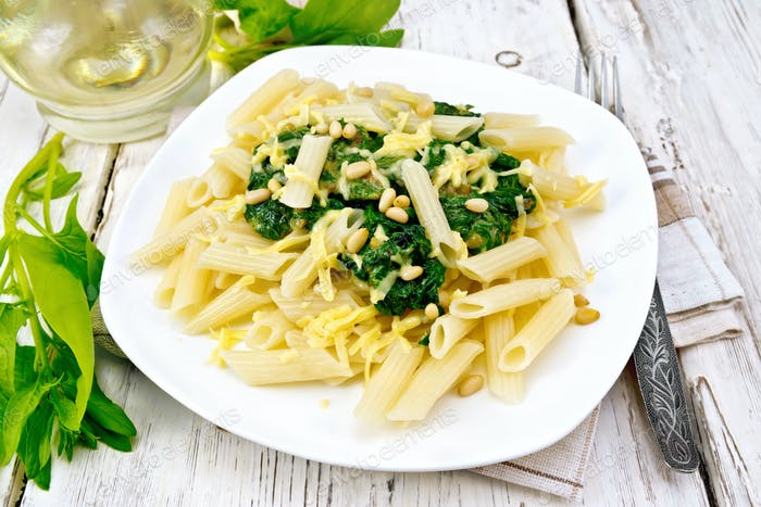 Pasta penne with spinach and nuts on board