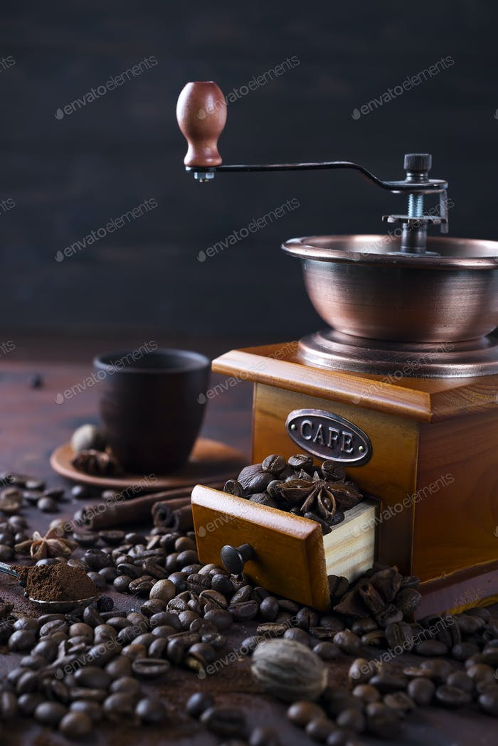 Old vintage grinder with roasted coffee beans and grind coffee on stone background.