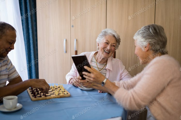 Smiling friends playing chess and using technology