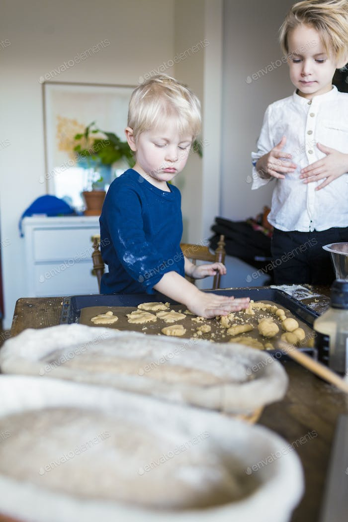 Brothers baking cookies at home