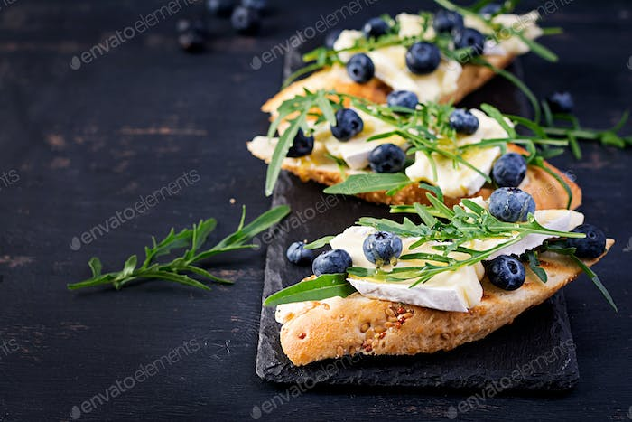 Bruschetta. Toast crostini with fresh berries blueberry and honey, brie cheese, arugula.