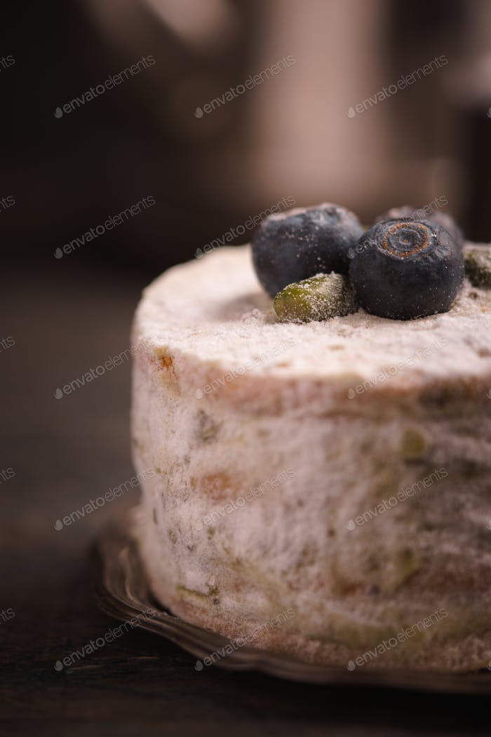 Cake with blueberries on the wooden table vertical