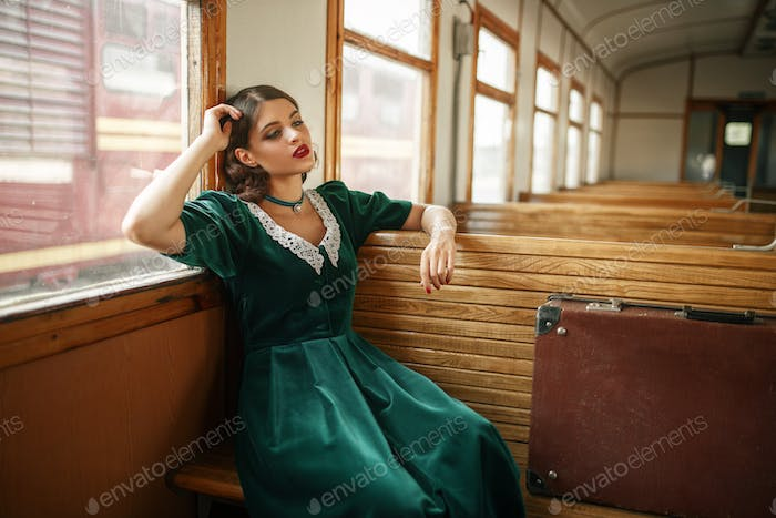 Female traveler in retro train, old wagon interior