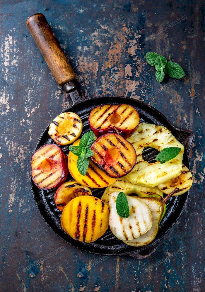 Gegrillte Früchte - Ananas, Pfirsiche, Pflaumen, Avocadobirne auf schwarzem Gusseisen Grillpfanne