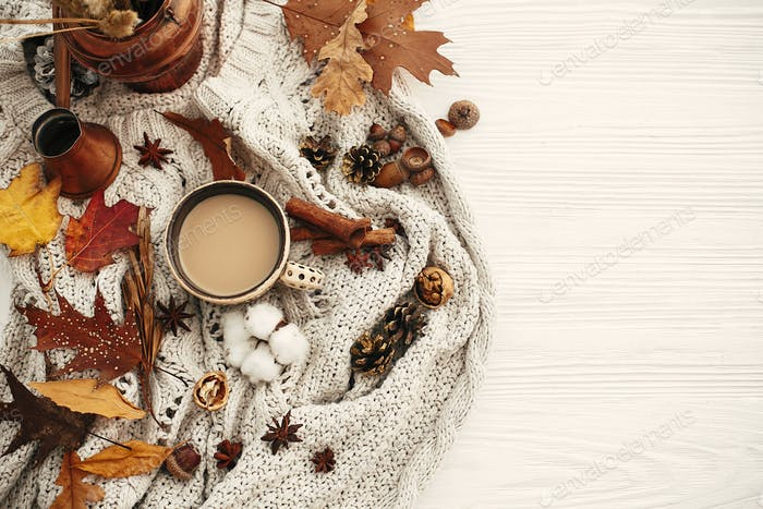 Autumn flat lay, cozy inspirational image.Hygge lifestyle. Coffee cup with  fall leaves