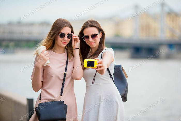 Caucasian girls making selfie background big bridge. Young tourist friends traveling on holidays