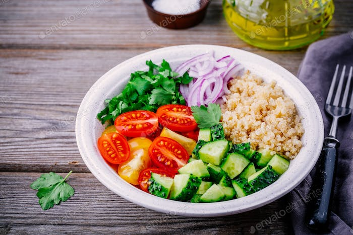 Healthy Quinoa Tabbouleh Salad bowl with fresh cucumbers, tomatoes and red onions