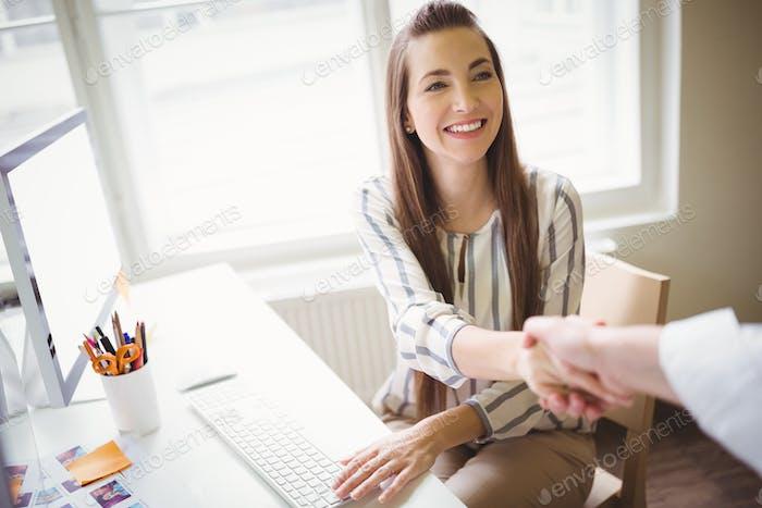 Persona estrechando la mano con la mujer de negocios en la oficina