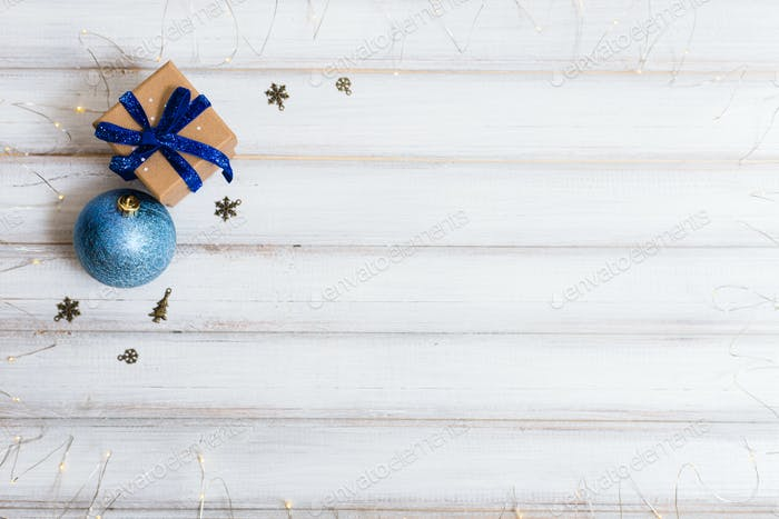 Christmas gift box and branch christmas tree and ball toy and cone on white wooden background