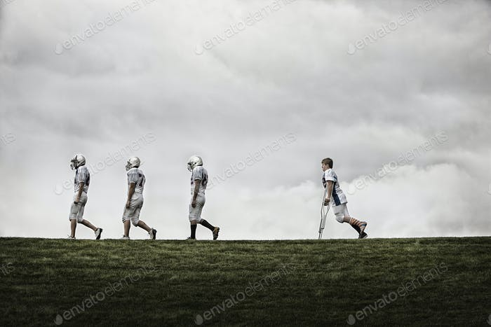 A group of football players, walking in line, one using crutches.