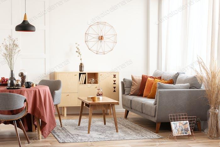 Wohn- und Esszimmer Interieur mit grauer Couch und Tisch mit orangefarbener Tischdecke bedeckt