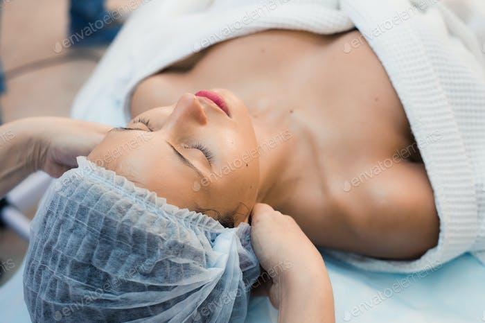 Young woman enjoying facial at spa salon