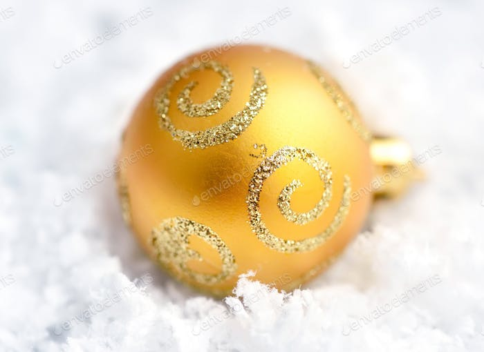 Christmas golden ball on snow. Close-up