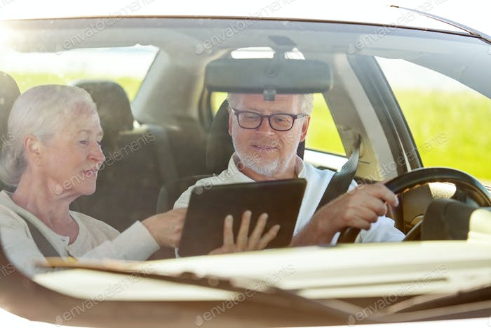 happy senior couple with tablet pc driving in car
