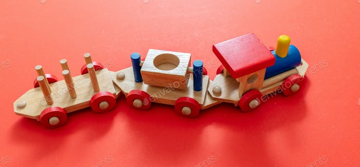 Train toy, wooden colorful blocks construction on red color background