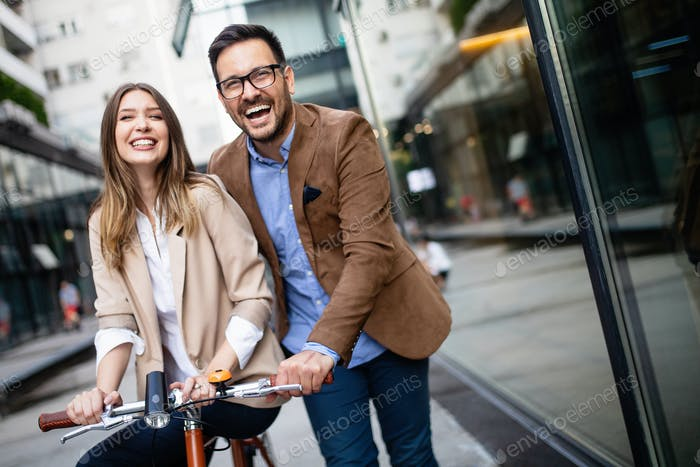 Young couple having fun in the city and ride a bicycle