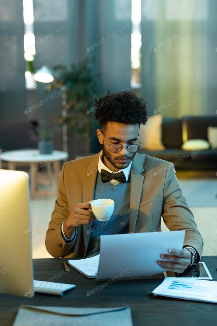 Busy man analyzing graphs over cup of coffee