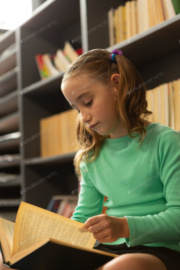 Cute schoolgirl sitting on floor and reading a book in library at elementary school