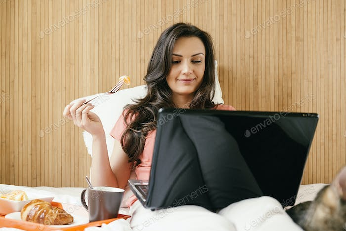 Woman working with her laptop computer and having breakfast