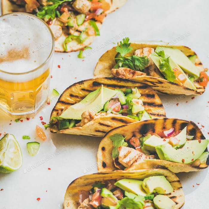Healthy corn tortillas with grilled chicken, avocado and wheat beer