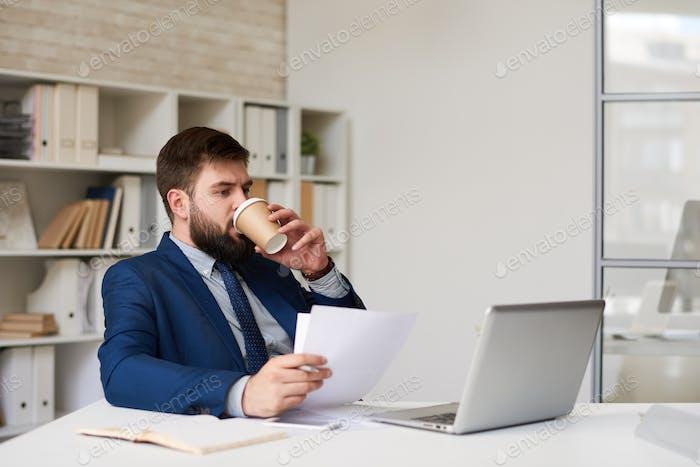 Modern Businessman Drinking Coffee in Office