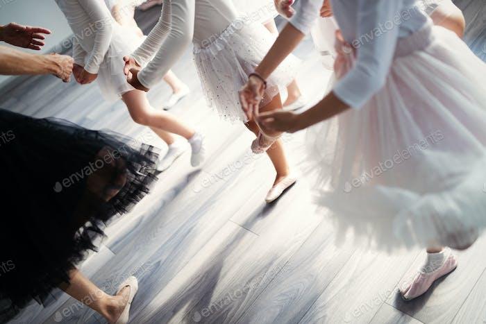 Ballet teacher and group of children ballerinas exercising in ballet studio