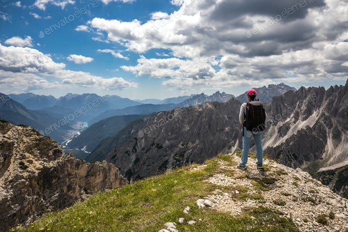 Hiker woman standing up achieving the top Dolomites Alps.