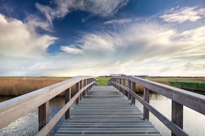 Holzbrücke über Fluss und blauer Himmel