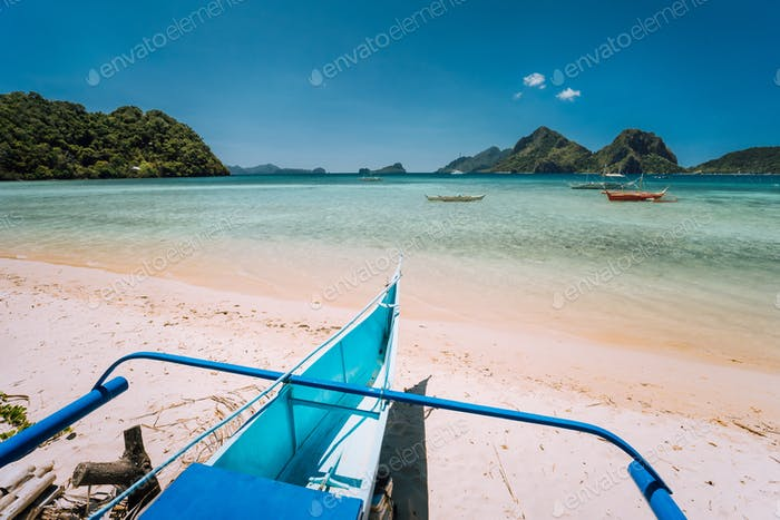 Traditional banca boat at Las cabanas beach in front of blue lagoon and exotic nature scenery in El