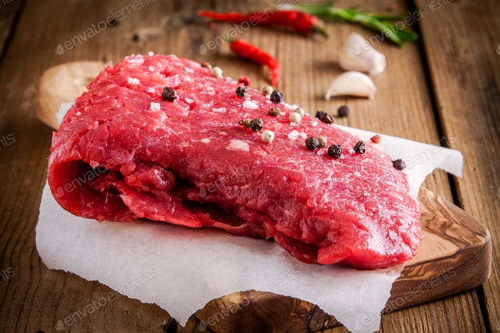raw meat steak on a cutting board with garlic and pepper