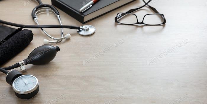 Medizinisches Stethoskop und Blutdruckmessgerät auf hölzernem Hintergrund