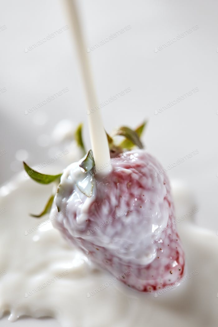 Ripe strawberries are watered with milk. Ingredients for a Healthy dairy dessert. Top view