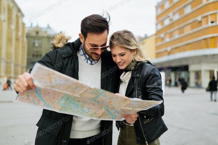 Smiling young attractive couple looking at map