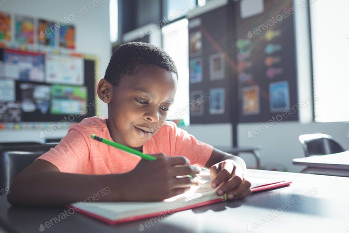 Boy writing in book at desk