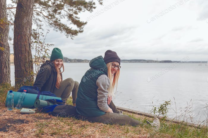 Smiling young women resting during traveling near the lake
