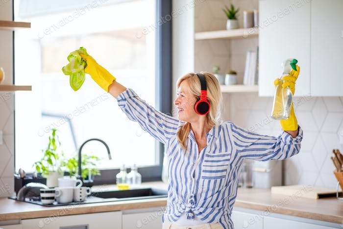 Portrait of senior woman with headphones and gloves cleaning indoors at home