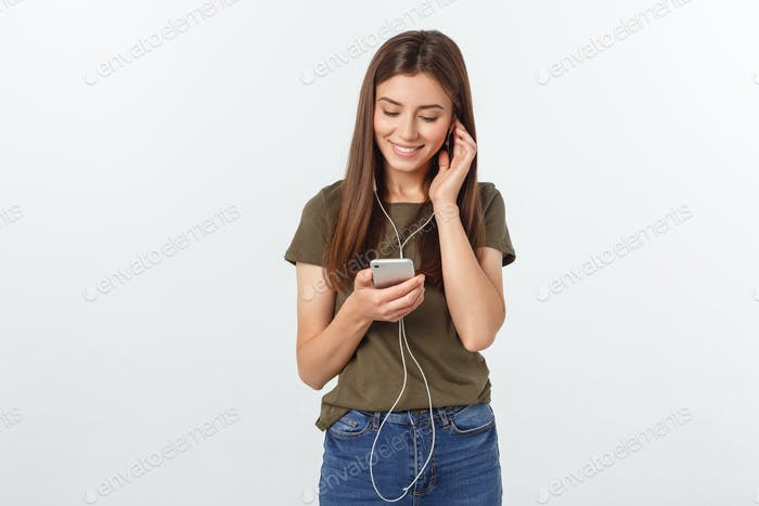 Portrait of a cheerful cute woman listening music in headphones and dancing isolated on a white