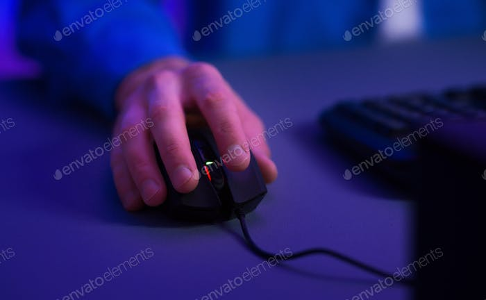Gamer hand on computer mouse, blue neon light from computer