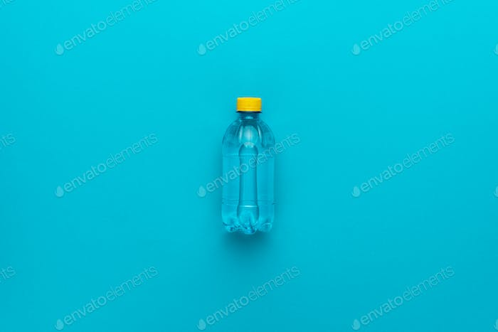 Plastic Water Bottle With Yellow Cap On The Blue Background