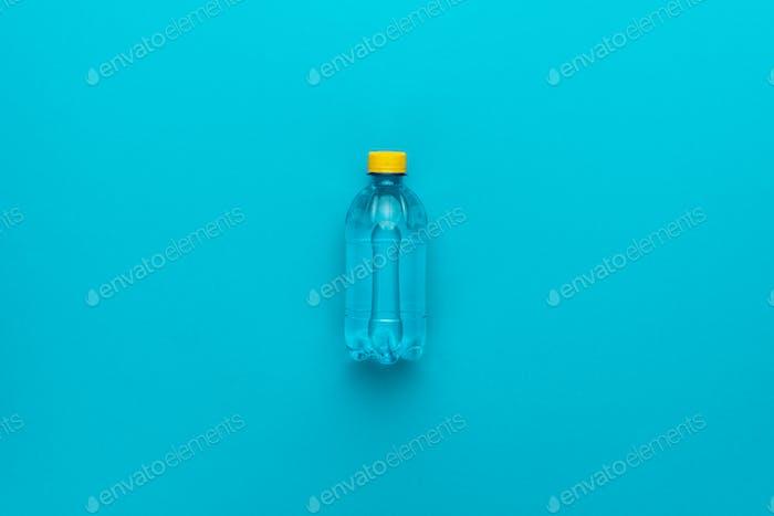 Plastikflasche mit gelber Kappe auf blauem Hintergrund